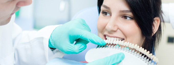 dentist matching tooth color for smile makeover on patient